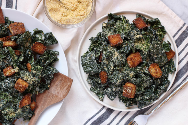 Vegan Kale Caesar Salad with tangy garlic tahini dressing, cashew parmesan, and whole grain croutons.